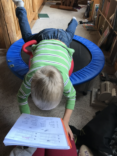 Child reading on a trampoline
